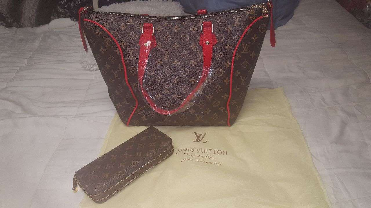 Photo Louis Vuitton handbag with matching wallet and red handles and red on the inside.